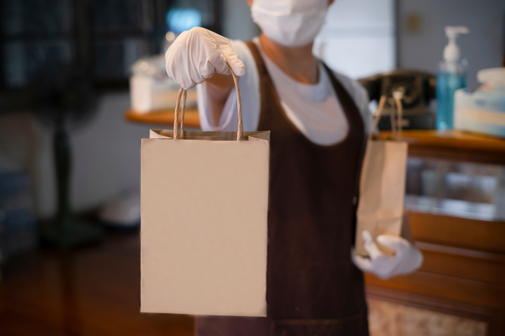 new normal an asian woman wearing gloves and medical face masks delivering take away food bags to cu